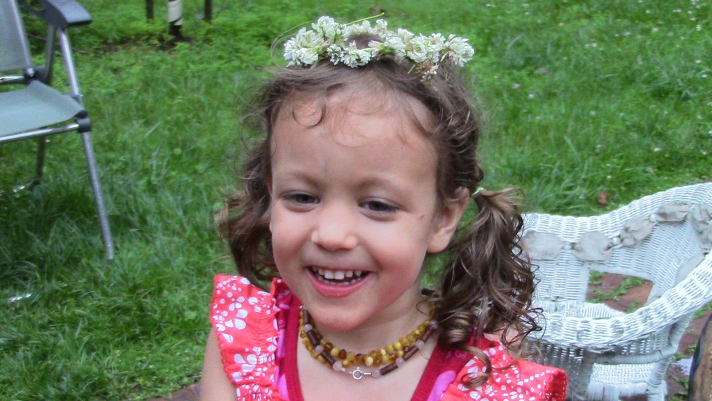 """This is my daughter """"smiling"""" with a hairstyle chosen by her (surprise) when she spontaneously went hunting for two hairbands to put her hair in two ponytails. (Her grandmother wave the flower wreath.)"""