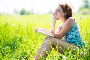 http://www.dreamstime.com/royalty-free-stock-photo-pretty-smiling-woman-book-nature-looking-away-image31793635